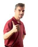 Der hohe und lächelnde Daumen des jungen Mannes trennte auf Weiß Stockfotos