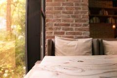Der Holztisch und das unscharfe Sofa neben einem Fenster der Kaffeestube Stockfotografie