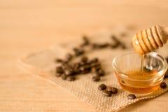 der Honigschöpflöffel und der wohlriechende Honig in eine transparente Schüssel mit Stockbilder
