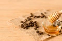 der Honigschöpflöffel und der wohlriechende Honig in eine transparente Schüssel mit Lizenzfreie Stockbilder