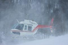 Der Hubschrauber landete in den Bergen im Winter und hob ein clou an Lizenzfreies Stockfoto