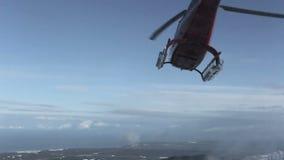 Der Hubschrauber ließ Skifahrer auf der Steigung des Berges und flog, eine Wolke des Schnees anhebend stock video