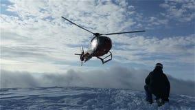 Der Hubschrauber ließ Skifahrer auf der Steigung des Berges und flog, eine Wolke des Schnees anhebend stock video footage