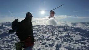 Der Hubschrauber ließ Skifahrer auf der Steigung des Berges und flog, eine Wolke des Schnees anhebend stock footage
