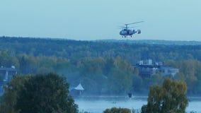 Der Hubschrauber sammelt Wasser im Fluss, um ein Feuer auszulöschen Der Rettungsdienst und die Feuerwehrmänner löschen das Feuer  stock video