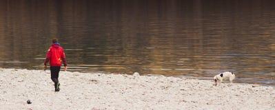 Der Hund und der Eigentümer spielen neben dem See; NEUSEELAND, IM APRIL 2017 lizenzfreie stockfotografie