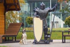 Der Hund und der Ritter in der schweren Rüstung das Gebäude schützend Stockfotos