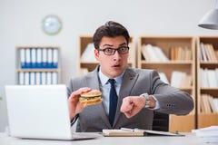 Der hungrige lustige Geschäftsmann, der Sandwich der ungesunden Fertigkost isst Stockfotografie