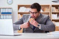 Der hungrige lustige Geschäftsmann, der Sandwich der ungesunden Fertigkost isst Lizenzfreie Stockbilder