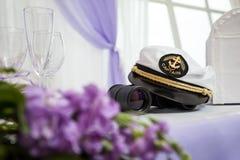 Der Hut des Kapitäns auf dem Tisch mit Ferngläsern und Blumen Lizenzfreie Stockbilder