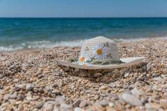 Der Hut mit Blumen auf dem Seehintergrund Stockfotos