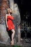 Der im Freien schönes Foto der jungen Frau Mode nahe altem GEHÖFT-Sommer Porträtmädchenblondinen im roten Kleid Lizenzfreies Stockbild