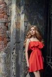 Der im Freien schönes Foto der jungen Frau Mode nahe altem GEHÖFT-Sommer Porträtmädchenblondinen im roten Kleid Stockfoto