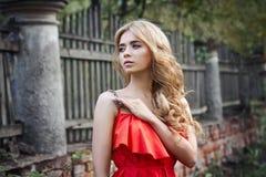 Der im Freien schönes Foto der jungen Frau Mode nahe altem GEHÖFT-Sommer Porträtmädchenblondinen im roten Kleid Lizenzfreies Stockfoto