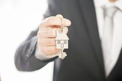 Der Immobilienmakler, der Hausschlüssel auf einem silbernen Haus gibt, formte keychain Stockfotografie
