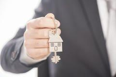 Der Immobilienmakler, der Hausschlüssel auf einem silbernen Haus gibt, formte keychain Stockfoto