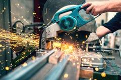 Der Industriearbeiter, der eine Verbundgehrungsfuge verwendet, sah mit scharfer Klinge Stockbild