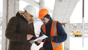 Der Ingenieur überprüft den Fortschritt auf Bau auf Baustelle im Winter Ingenieur, der mit dem Vorarbeiter auf spricht stock video footage