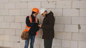 Der Ingenieur überprüft den Fortschritt auf Bau auf Baustelle im Winter Ingenieur, der mit dem Vorarbeiter auf spricht stock footage