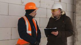 Der Ingenieur überprüft den Fortschritt auf Bau auf Baustelle im Winter Ingenieur, der mit dem Vorarbeiter auf spricht stock video