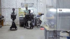Der Ingenieur stellt her und justiert den modernen Roboter stock video footage