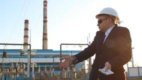 Der Ingenieurinspektor in den Handschellen hält Geld vor dem hintergrund des Kraftwerks und ist empört stock video