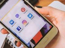 Der Inhaber benutzt das Telefon für Kommunikation und Spiel und das Sitzen auf Social Media Lizenzfreie Stockfotografie