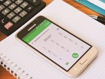 Der Inhaber benutzt das Telefon für Kommunikation und Spiel und das Sitzen auf Social Media Stockbilder