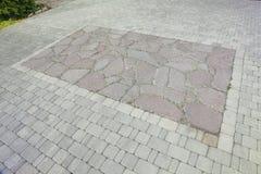 Der Innenhof wird mit dekorativem Stein gepflastert Steinpflasterung, gepflasterte rechteckige Rotblöcke Eine Steinplasterung Stockfotografie