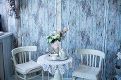 Der Innenraum in den blauen Tönen mit zwei Stühlen und einem Vase mit flowe Stockfotografie