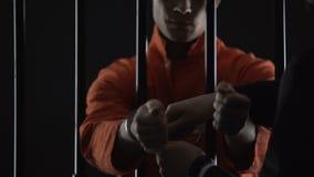 Der Insasse, der auf Gefängnis gesetzt wird, fesselt Warteversuch, Verbrechenbestrafung, Gesetzesbrechen mit Handschellen stock video