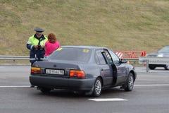 Der Inspektor der Verkehrspolizei auf der Autobahn sprechend mit einem weiblichen Fahrer Lizenzfreie Stockbilder