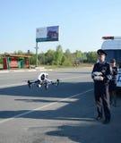 Der Inspektor von Verkehrspolizeidienstleistungen überwacht den Weg unter Verwendung des quadcopter Lizenzfreie Stockbilder
