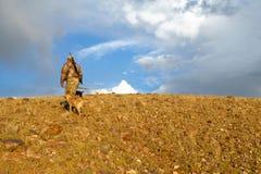 Der Jäger und Hunde, die im trockenen Sonnenaufgang wandern, gestalten landschaftlich Stockbild