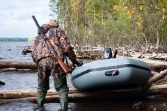 Der Jäger zieht das Boot auf dem Wasser Lizenzfreie Stockfotos