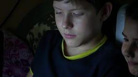 Der jugendlich Junge und das Mädchen spielt auf dem Laptop an den Nachtonline-spielen stock footage