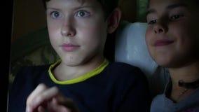 Der jugendlich Junge und das Mädchen spielt auf dem Laptop Nachtan den on-line-Computerspielen stock footage