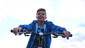 Der Jugendliche, der ein Fahrrad reitet, tuend trägt in der Frischluft zur Schau Reise und aktive Unterhaltung Momente der glückl stock footage
