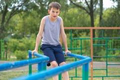 Der Jugendliche in einer Weste wird auf Stufenbarren engagiert lizenzfreie stockbilder