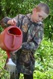Der Jugendliche hält eine Gießkanne Stockfoto