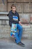 Der Jugendliche kostet an einer Wand mit einem Skateboard Lizenzfreies Stockfoto