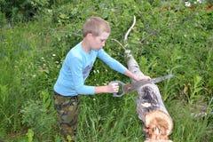 Der Jugendliche mit einer Metallsäge an einem Baum Stockfotografie