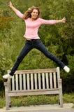 Der Jugendliche springend von einer Bank mit den Armen heraus stockbilder