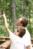 Der Jugendlichjunge und sein Vater, die am Sommer wandern, parken Stockfotografie
