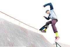 Der Jugendlichskateboardfahrer in der Kappe tut einen Trick mit einem Sprung auf der Rampe im skatepark Lokalisierter Schlittschu lizenzfreie stockfotos
