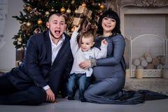 Der Junge öffnet das Geschenk zu den Eltern am Weihnachten lizenzfreies stockfoto