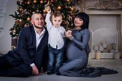 Der Junge öffnet das Geschenk zu den Eltern am Weihnachten stockfoto