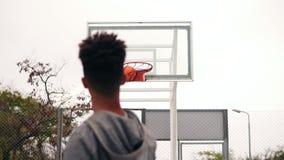 Der junge afrikanische Spieler, der oben springen und der werfende Ball in einem Basketballkorb, der Ball schlägt den Ring und di stock video