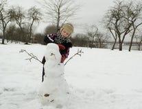 Der Junge arbeitet mit Sorgfalt sculpts einen Schneemann stockbilder