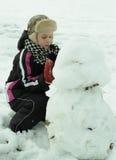 Der Junge arbeitet mit Sorgfalt sculpts einen Schneemann stockbild